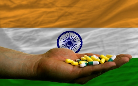 man holding capsules in front of complete wavy national flag of india symbolizing health, medicine, cure, vitamines and healthy life
