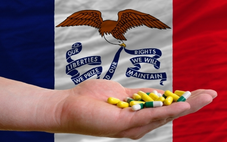 man holding capsules in front of complete wavy american state flag of iowa symbolizing health, medicine, cure, vitamines and healthy life photo