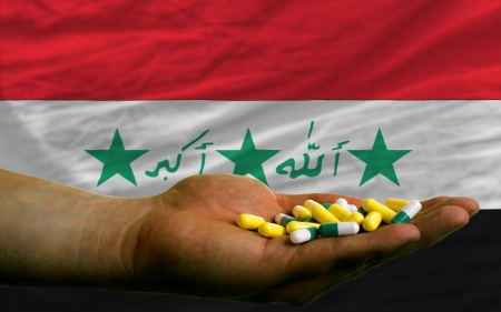 man holding capsules in front of complete wavy national flag of iraq symbolizing health, medicine, cure, vitamines and healthy life photo