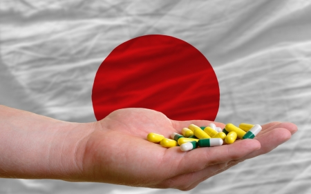 man holding capsules in front of complete wavy national flag of japan symbolizing health, medicine, cure, vitamines and healthy life photo