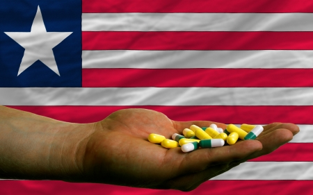 man holding capsules in front of complete wavy national flag of liberia symbolizing health, medicine, cure, vitamines and healthy life photo