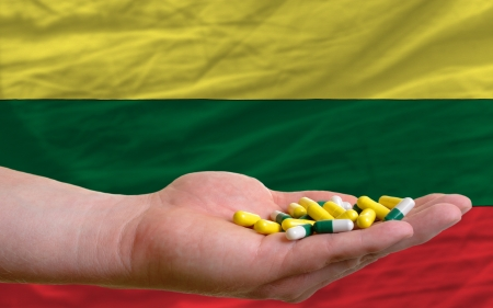 man holding capsules in front of complete wavy national flag of lithuania symbolizing health, medicine, cure, vitamines and healthy life photo