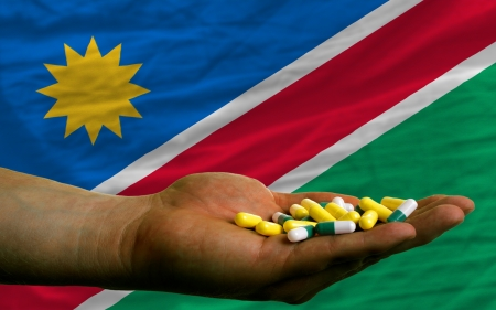 vitamines: man holding capsules in front of complete wavy national flag of namibia symbolizing health, medicine, cure, vitamines and healthy life
