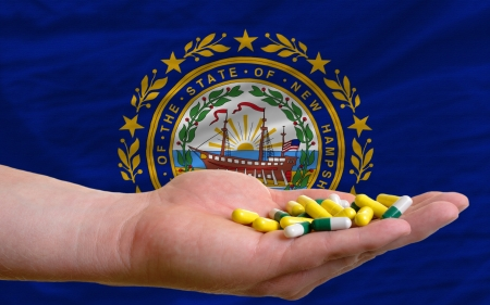 new medicine: man holding capsules in front of complete wavy american state flag of new hampshire symbolizing health, medicine, cure, vitamines and healthy life Stock Photo