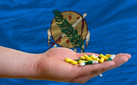 man holding capsules in front of complete wavy american state flag of oklahoma symbolizing health, medicine, cure, vitamines and healthy life photo