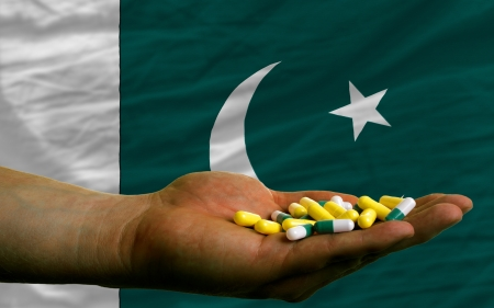 man holding capsules in front of complete wavy national flag of pakistan symbolizing health, medicine, cure, vitamines and healthy life Stock Photo - 14428204