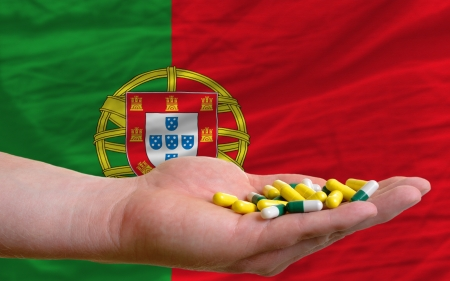 man holding capsules in front of complete wavy national flag of portugal symbolizing health, medicine, cure, vitamines and healthy life photo