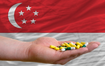 vitamines: man holding capsules in front of complete wavy national flag of singapore symbolizing health, medicine, cure, vitamines and healthy life Editorial