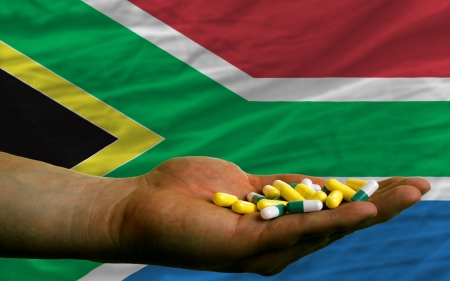 man holding capsules in front of complete wavy national flag of south africa symbolizing health, medicine, cure, vitamines and healthy life photo
