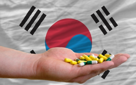 man holding capsules in front of complete wavy national flag of south korea symbolizing health, medicine, cure, vitamines and healthy life photo