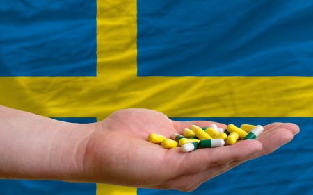 man holding capsules in front of complete wavy national flag of sweden symbolizing health, medicine, cure, vitamines and healthy life photo