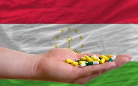 vitamines: man holding capsules in front of complete wavy national flag of tajikistan symbolizing health, medicine, cure, vitamines and healthy life Stock Photo