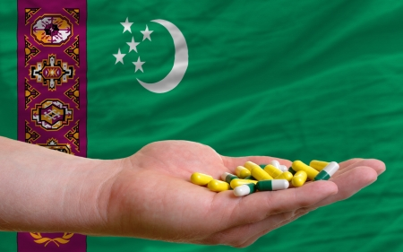 turkmenistan: man holding capsules in front of complete wavy national flag of turkmenistan symbolizing health, medicine, cure, vitamines and healthy life