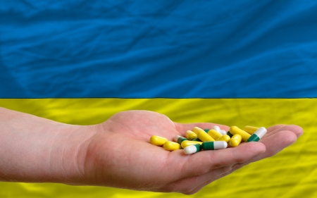 man holding capsules in front of complete wavy national flag of ukraine symbolizing health, medicine, cure, vitamines and healthy life photo