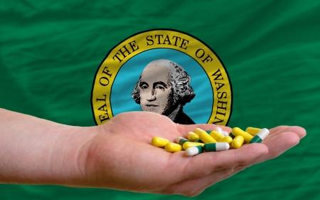 washington state: man holding capsules in front of complete wavy american state flag of washington symbolizing health, medicine, cure, vitamines and healthy life Stock Photo