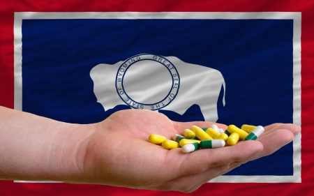 man holding capsules in front of complete wavy american state flag of wyoming symbolizing health, medicine, cure, vitamines and healthy life Stock Photo - 15002935