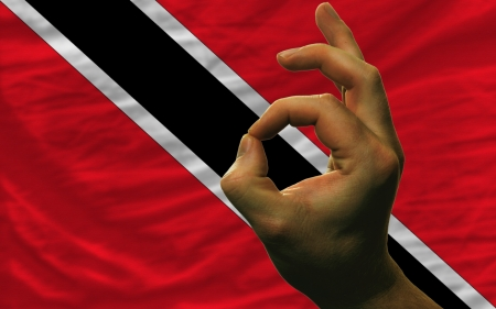 man showing excellence or ok gesture in front of complete wavy trinidad tobago national flag of  symbolizing best quality, positivity and succes photo