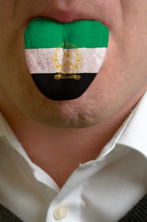 man wit open mouth spreading tongue colored in afghanistan flag as symbol of values like teaching, learning, multilingual speaking of different languages Stock Photo - 15002824