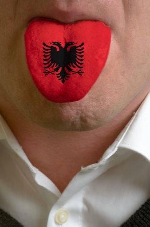 albanian: man wit open mouth spreading tongue colored in albania flag as symbol of values like teaching, learning, multilingual speaking of different languages