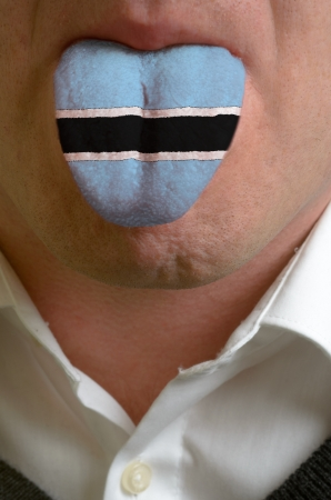 botswanan: man wit open mouth spreading tongue colored in botswana flag as symbol of values like teaching, learning, multilingual speaking of different languages Stock Photo