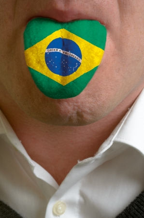 man wit open mouth spreading tongue colored in brazil flag as symbol of values like teaching, learning, multilingual speaking of different languages Stock Photo - 15002820