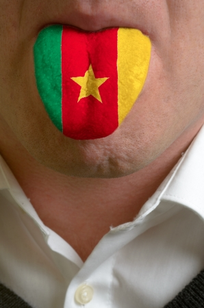 man wit open mouth spreading tongue colored in cameroon flag as symbol of values like teaching, learning, multilingual speaking of different languages photo