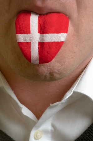 man wit open mouth spreading tongue colored in denmark flag as symbol of values like teaching, learning, multilingual speaking of different languages photo