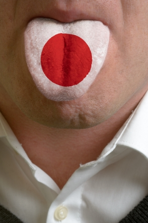 man wit open mouth spreading tongue colored in japan flag as symbol of values like teaching, learning, multilingual speaking of different languages Stock Photo - 15002808