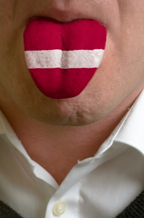 man with open mouth spreading tongue colored in latvia flag as symbol of values like teaching, learning, multilingual speaking of different languages Stock Photo - 15002748