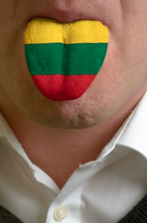 man with open mouth spreading tongue colored in lithuania flag as symbol of values like teaching, learning, multilingual speaking of different languages photo