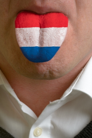 man with open mouth spreading tongue colored in netherlands flag as symbol of values like teaching, learning, multilingual speaking of different languages Stock Photo - 15002811