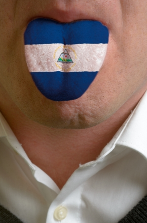 man wit open mouth spreading tongue colored in nicaragua flag as symbol of values like teaching, learning, multilingual speaking of different languages Stock Photo - 15002814