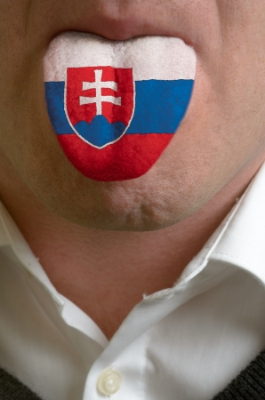 man wit open mouth spreading tongue colored in slovakia flag as symbol of values like teaching, learning, multilingual speaking of different languages photo