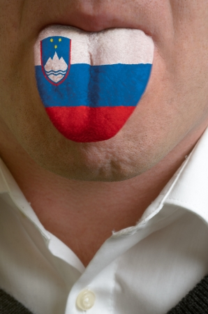 man wit open mouth spreading tongue colored in slovenia flag as symbol of values like teaching, learning, multilingual speaking of different languages photo