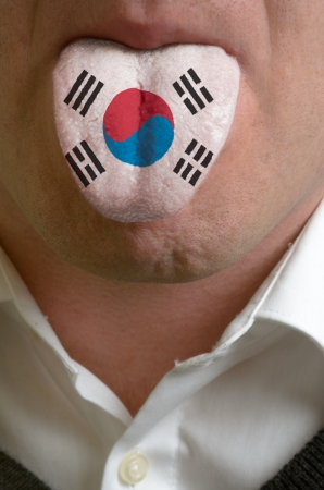 man wit open mouth spreading tongue colored in south korea flag as symbol of values like teaching, learning, multilingual speaking of different languages Stock Photo - 15002837