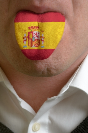 multilingual: man wit open mouth spreading tongue colored in spain flag as symbol of values like teaching, learning, multilingual speaking of different languages