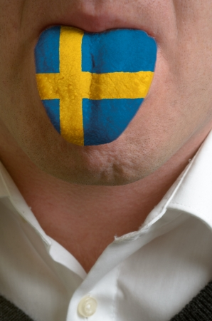 man wit open mouth spreading tongue colored in sweden flag as symbol of values like teaching, learning, multilingual speaking of different languages photo