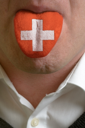 man wit open mouth spreading tongue colored in switzerland flag as symbol of values like teaching, learning, multilingual speaking of different languages Stock Photo - 15002800