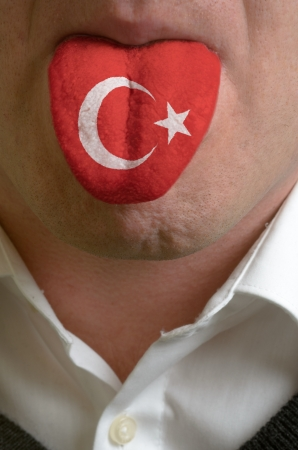 man wit open mouth spreading tongue colored in turkey flag as symbol of values like teaching, learning, multilingual speaking of different languages photo