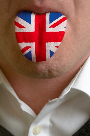 learn english: man wit open mouth spreading tongue colored in great britain flag as symbol of values like teaching, learning, multilingual speaking different of languages