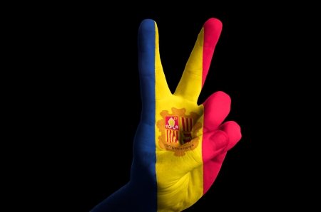 tourism in andorra: Hand with two finger up gesture in colored andorra national flag as symbol of winning, victorious, excellent, - for tourism and touristic advertising, positive political, cultural, social management of country Stock Photo