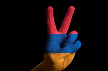 Hand with two finger up gesture in colored armenia national flag as symbol of winning, victorious, excellent, - for tourism and touristic advertising, positive political, cultural, social management of country photo