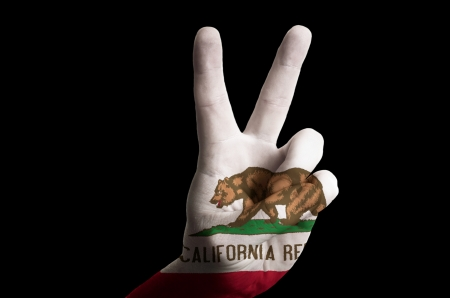 Hand with two finger up gesture in colored california state flag as symbol of winning, victorious, excellent, - for tourism and touristic advertising, positive political, cultural, social management of country photo