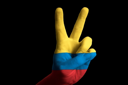 colombian flag: Hand with two finger up gesture in colored colombia national flag as symbol of winning, victorious, excellent, - for tourism and touristic advertising, positive political, cultural, social management of country Stock Photo