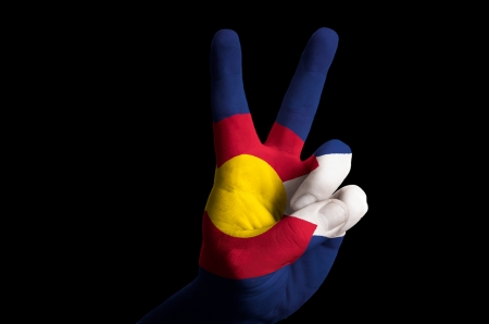 Hand with two finger up gesture in colored colorado state flag as symbol of winning, victorious, excellent, - for tourism and touristic advertising, positive political, cultural, social management of country photo