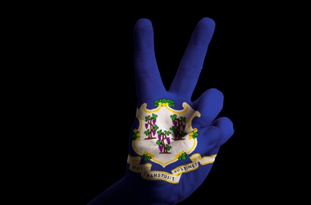 Hand with two finger up gesture in colored connecticut state flag as symbol of winning, victorious, excellent, - for tourism and touristic advertising, positive political, cultural, social management of country photo