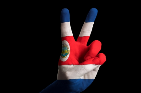 Hand with two finger up gesture in colored costa rica national flag as symbol of winning, victorious, excellent, - for tourism and touristic advertising, positive political, cultural, social management of country photo