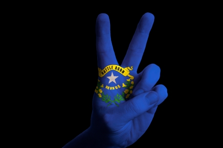 Hand with two finger up gesture in colored nevada state flag as symbol of winning, victorious, excellent, - for tourism and touristic advertising, positive political, cultural, social management of country photo