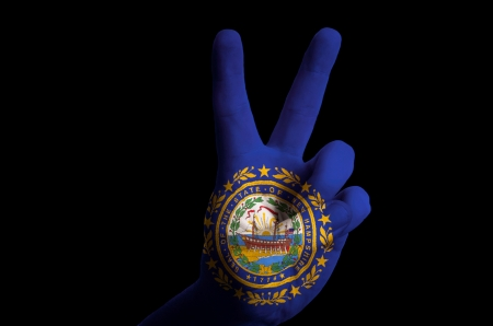 Hand with two finger up gesture in colored new hampshire state flag as symbol of winning, victorious, excellent, - for tourism and touristic advertising, positive political, cultural, social management of country photo