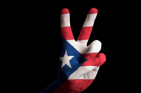 Hand with two finger up gesture in colored puertorico national flag as symbol of winning, victorious, excellent, - for tourism and touristic advertising, positive political, cultural, social management of country Stock Photo - 15001340